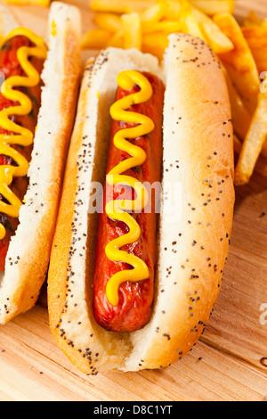 Organic All Beef Hotdog on a bun with mustard - Stock Photo