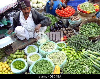 Indian street vendor selling selling fresh vegetables and fruits in farmer's market , Ahmedabad, India - Stock Photo