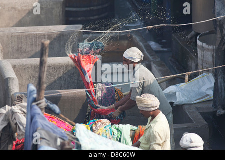 A man hand washing clothes in Dhobi Ghat, a well known open air laundromat in Mumbai, India - Stock Photo