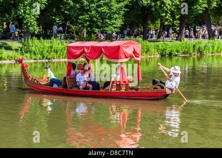 Tourists enjoy a gondola trip on the lake in Łazienki Park Łazienkowski, the largest in Warsaw. - Stock Photo