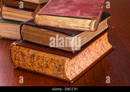 Old Books on Dark Wood Background - battered old books on a dark oak table, focus on foreground. - Stock Photo