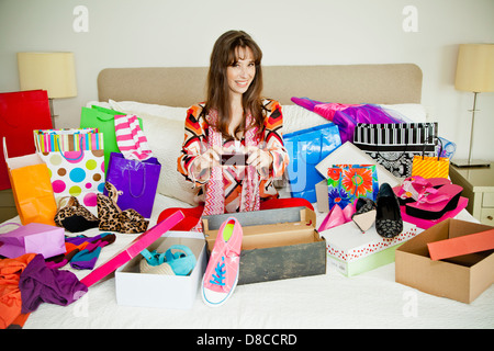 Woman on bed surrounded by shopping bags - Stock Photo