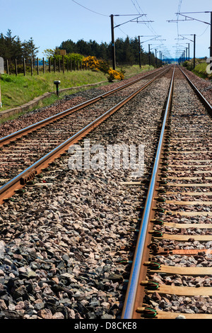 Railway tracks travelling into the distance with electric overhead cables, Scotland, UK - Stock Photo