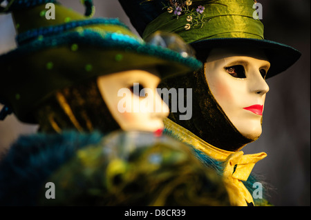 A couple wearing green carnival costumes and masks during the Venice Carnival, Italy. - Stock Photo