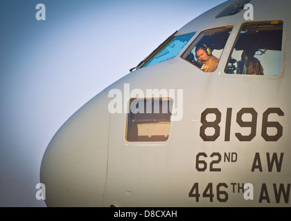 A US Air Force pilot performs pre-flight checks on a C-17 Globemaster III aircraft before departing Shindand Air - Stock Photo