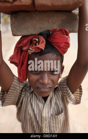 Dhaka,bangladesh 25th may 2013;'swapon' a 8 years old boy who collects bricks from street & sell them.every day - Stock Photo