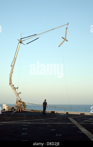 A US Navy Scan Eagle Unmanned Aircraft System aircraft is retrieved on board the amphibious transport dock ship - Stock Photo