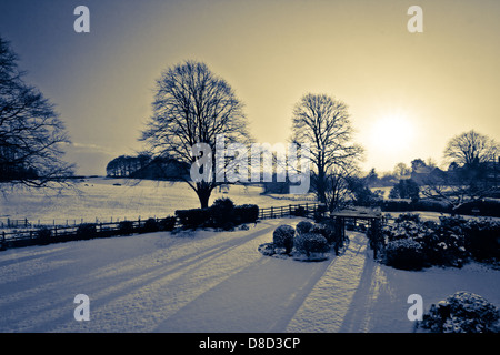 Snowy English countryside with bright Winter Sun over snow covered fields - Stock Photo