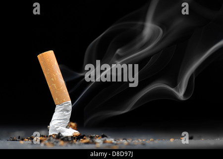 A burning cigarette with smoke against a black background. - Stock Photo