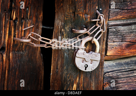 Old rusty padlock and chain on the rural wooden gate - Stock Photo