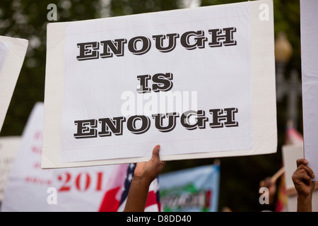 Man holding up an 'Enough is Enough' sign during protest - Stock Photo