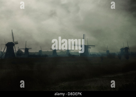 many windmills on a field in morning mist - Stock Photo