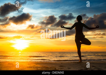 Girl practicing yoga by the sea at sunset. - Stock Photo