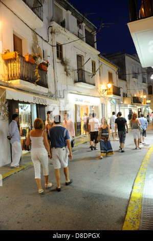 Holiday makers stroll through the streets Ibiza Town By Night - Stock Photo
