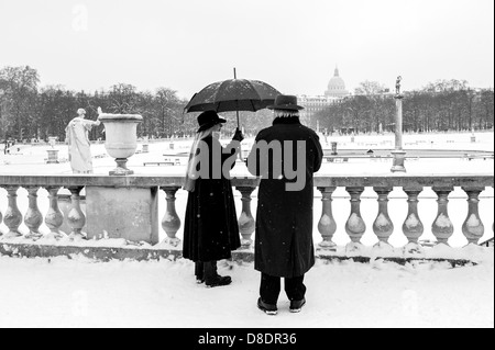 Senior couple enjoying snowy park. - Stock Photo
