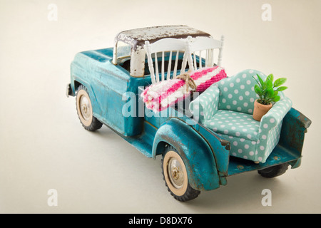 Old vintage toy truck packed with furniture - moving houses concept - Stock Photo