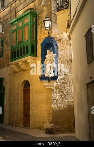 Mary Magdalene statue situated into the corner of building in Victoria on the Mediterranean Island of Gozo - Stock Photo