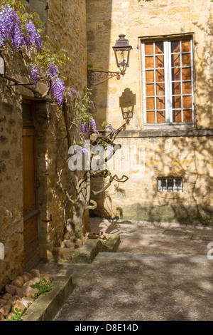 Wrought iron street lamp casting afternoon shadow on wall of medieval stone buildings in courtyard, Sarlat, Dordogne, - Stock Photo