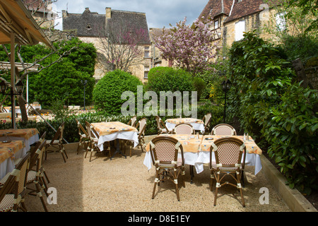 Outdoor courtyard dining at a restaurant by medieval sandstone buildings in charming Sarlat, Dordogne region of France