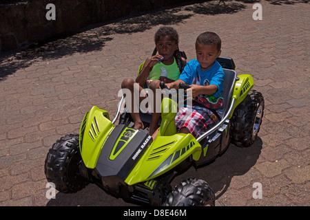 Little African American boy and girl riding a electrical go-cart, Finley Park, Santa Rosa, California, USA, North - Stock Photo