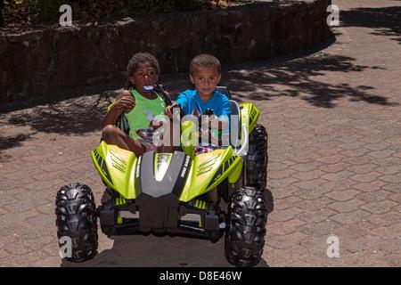 Little African American boy and girl riding an electrical go-cart, Finley Park, Santa Rosa, California, USA, North - Stock Photo