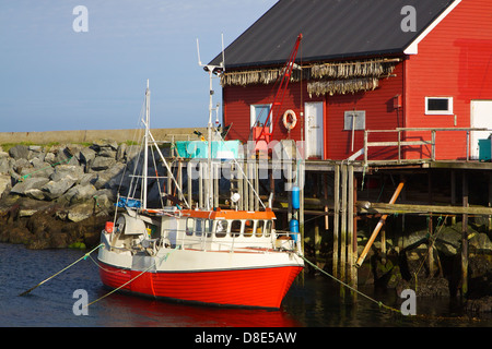 Typical norwegian fishing boat in port with dried stock fish hanging on the front wall - Stock Photo
