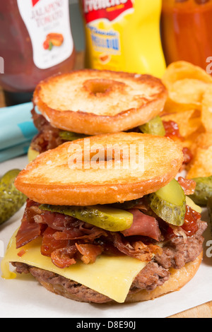 The Luther burger: a beef patty, cheese, crispy bacon and gherkins between two halves of a glazed ring doughnut. - Stock Photo