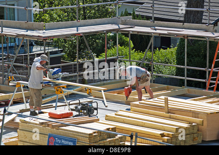 Two carpenters working on a new house - Stock Photo