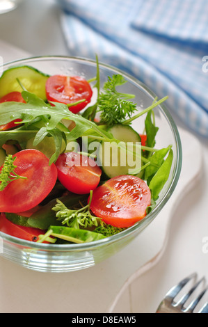fresh salad with tomatoes cherry, arugula and cucumber in glass bowl - Stock Photo