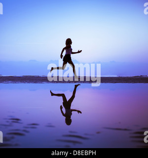 Female runner silhouette is mirrored below with a blue sunset sky as background - Stock Photo