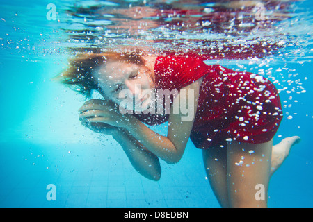 imagination, underwater portrait of woman in red dress - Stock Photo