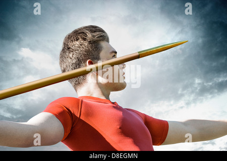 Attractive young man concentrates to throw his metallic javelin - Stock Photo