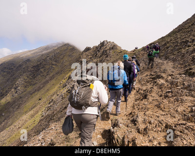 Ramblers walking on Rhyd Ddu path on Bwlch Main to Snowdon with view of peak shrouded in low cloud. Snowdonia North - Stock Photo