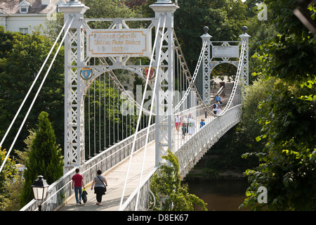 Walking a cross the Queens Park Suspension bridge over the River Dee in Chester, Cheshire - Stock Photo