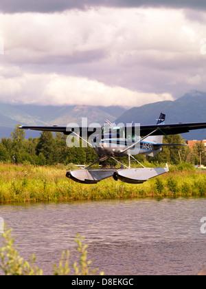 Cessna 206 float plane landing at lake Hood Sea plane Base in Anchorage Alaska - Stock Photo