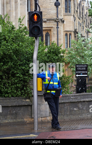 Civil Enforcement Officer waiting to cross road in the rain at Oxford in May - Stock Photo