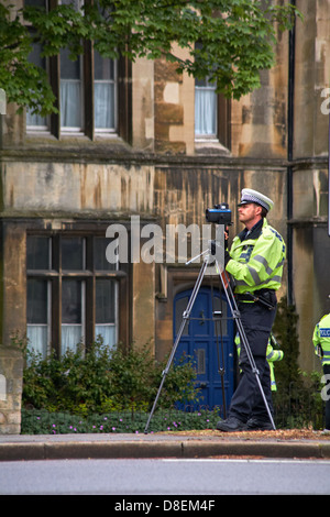 Traffic police officer with mobile speed camera on tripod checking speeding traffic at Oxford in May - Stock Photo