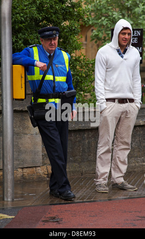Civil Enforcement Officer and man in hoodie waiting at the traffic lights in the rain at Oxford in May - Stock Photo
