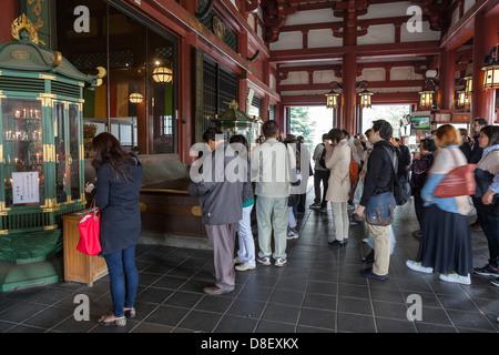 People in front of Bodhisattva Kannon statue in Main Hall of Senso-ji, Tokyo, Japan - Stock Photo