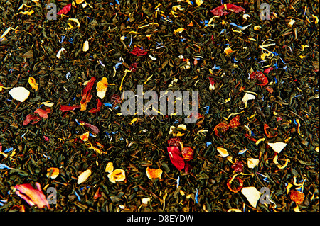 Dried tea leaves mixed with dried fruit as background - Stock Photo