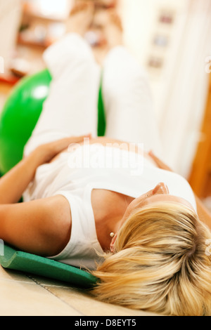 Pregnant woman doing pregnancy gymnastics or pilates lying on a fitness ball - Stock Photo