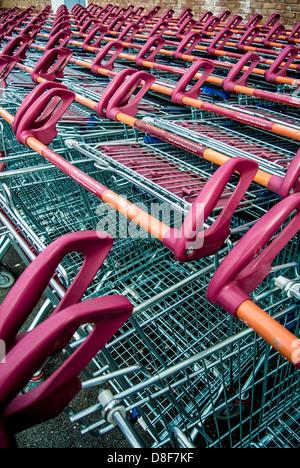Sainsburys shopping trolleys lined up outside supermarket - Stock Photo