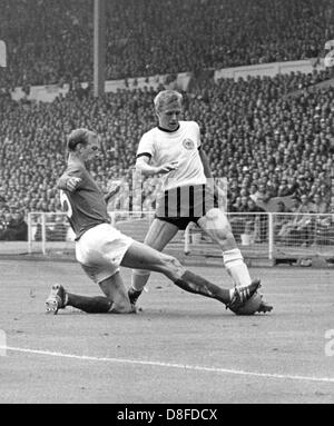 English defender Jack Charlton (L) stretches his leg and stops the approach of German forward Siegfried Held (R) - Stock Photo
