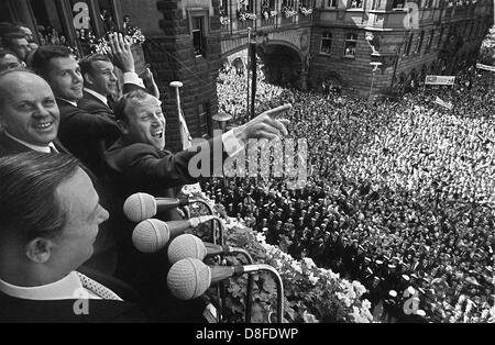An enthusiastic crowd of people at the Frankfurt Roemerberg are celebrating the German players who are standing - Stock Photo