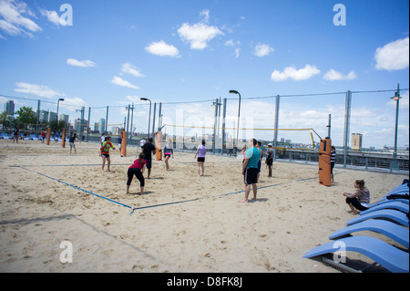 Sports enthusiasts play beach volleyball on the courts on Pier 25 in Hudson River Park in New York - Stock Photo
