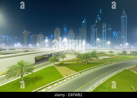 Skyscrapers and intersection on Sheikh Zayed Road at night in haze, New Dubai, UAE - Stock Photo