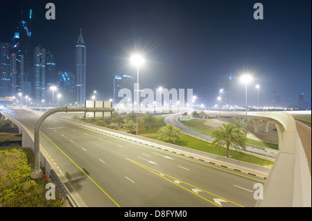 Motorway intersection on Sheikh Zayed Road, skyscrapers and nocturnal haze in Marina, New Dubai, UAE - Stock Photo