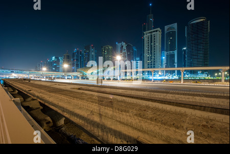 View construction site Al Soufouh Tram Systems in Marina skyscrapers Jumeirah Lakes Towers (JLT) night New Dubai - Stock Photo