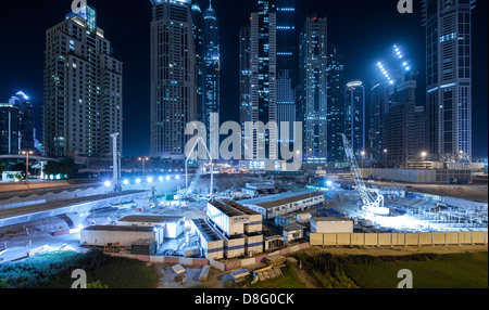Construction sites floodlighting and skyscrapers at night in Marina, New Dubai, UAE - Stock Photo