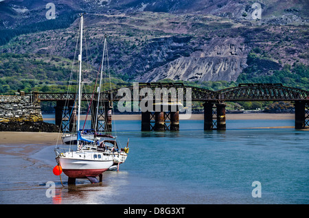 Barmouth Bridge and ships during low tide - Stock Photo